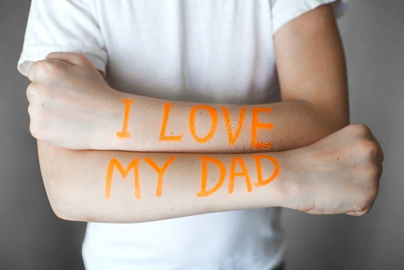 Orange Aufschrift auf den Händen eines Jugendlichen liebe ich meinen Vati stockfotos