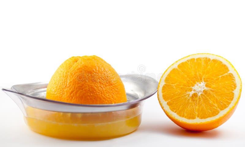 Orange avec le juicer. sur le blanc. photos stock