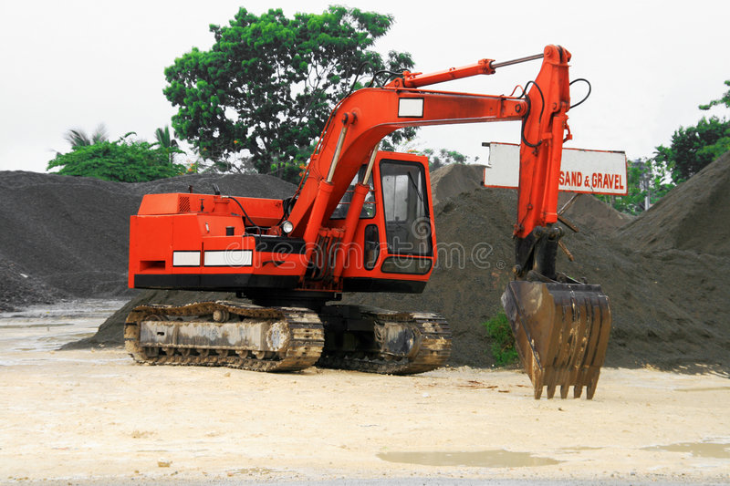 Orange back hoe. An orange back hoe parked near a heap of gravel and sand royalty free stock photo