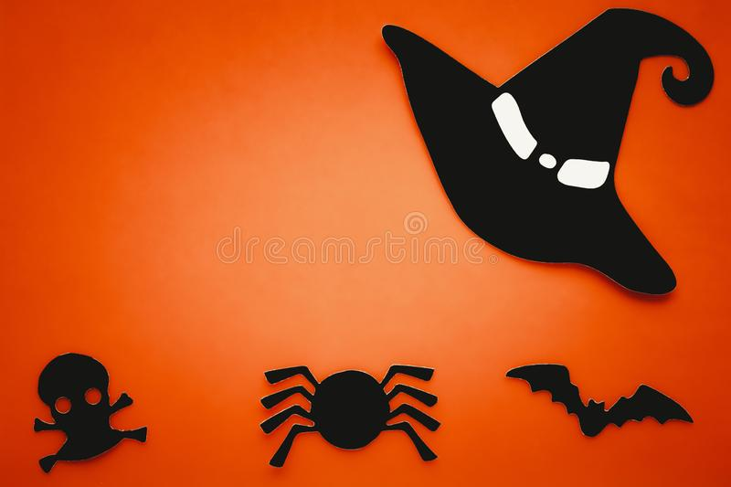Orange background with black silhouette of spider, bat, skull, witch hat. Halloween card, paper composition. Abstract art. Invitat stock image