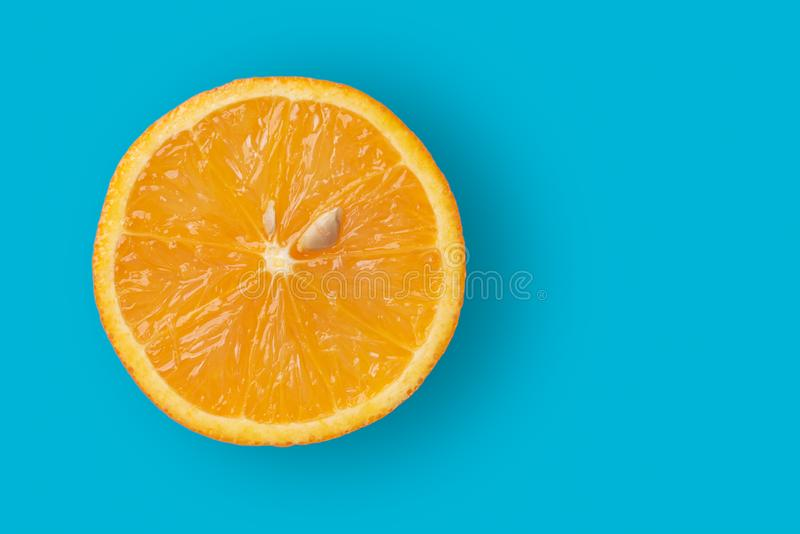 Closeup of half cut orange fruit on blue background. Copy space on right. Orange background. Closeup of half cut orange fruit on blue background. Copy space on stock photo