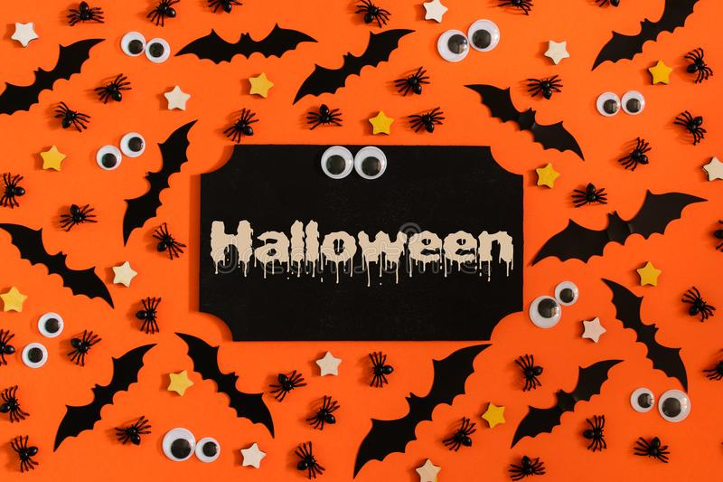 On the orange background are scattered doll eyes, decorative bats and spiders. In the center of the tablet, with the royalty free stock photo