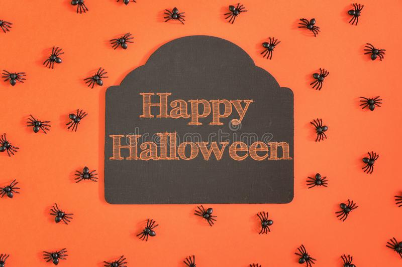 On an orange background a tablet with an inscription of Happy Halloween. Around a lot of small decorative spiders. An unusual photo from the top stock images