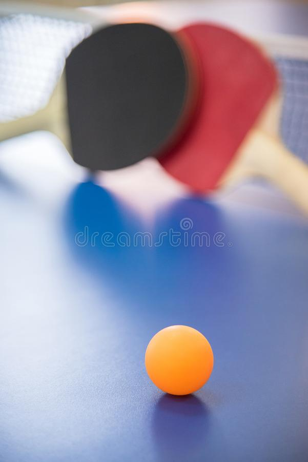 Orange ball for table tennis and two rackets of red and black co stock photography