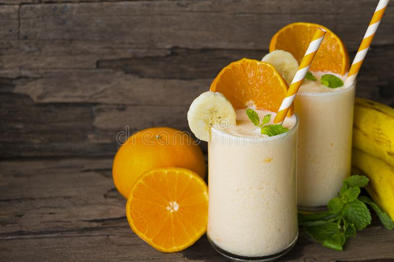 Orange and banana smoothies fruit on old wood background. Orange and banana smoothies orange colorful fruit juice beverage healthy high protein the taste yummy stock images