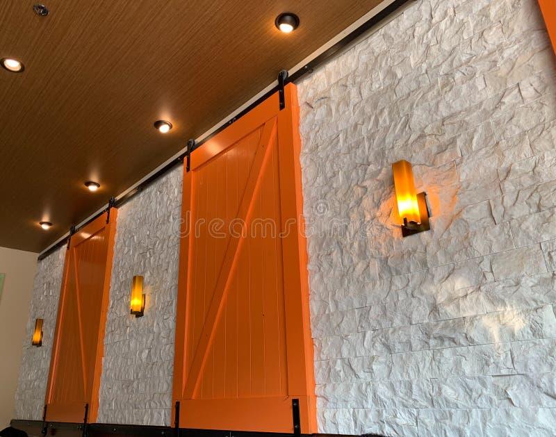Orange barn doors. Wall sconce decorative angle decor inside light lit royalty free stock photography