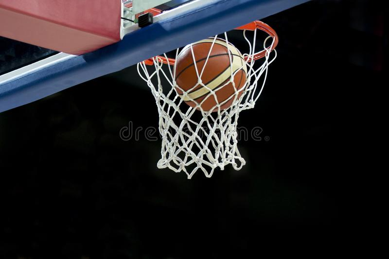 The orange basketball ball flies through the basket stock photography