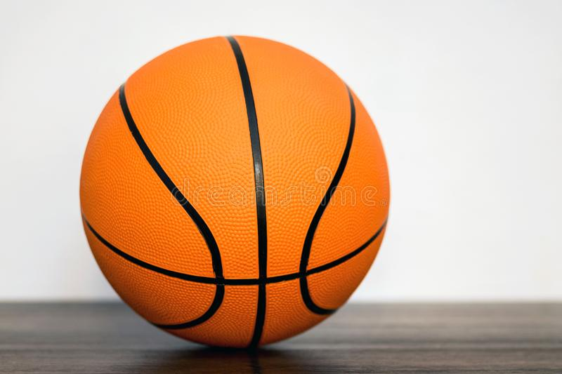 Orange basketball ball in the sports hall on the floor on blurry background_. Orange basketball ball in the sports hall on the floor on blurry background stock photo