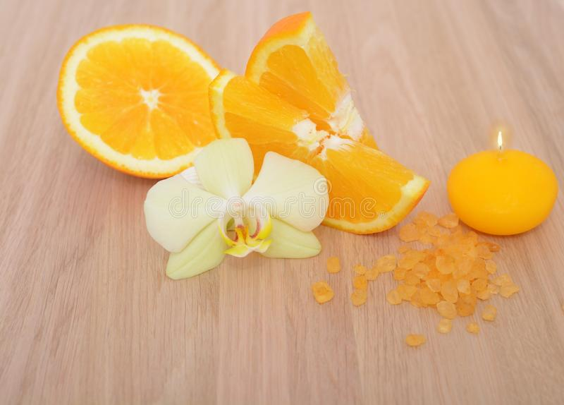 Orange bath salt orchid flower and candle on wooden background stock images