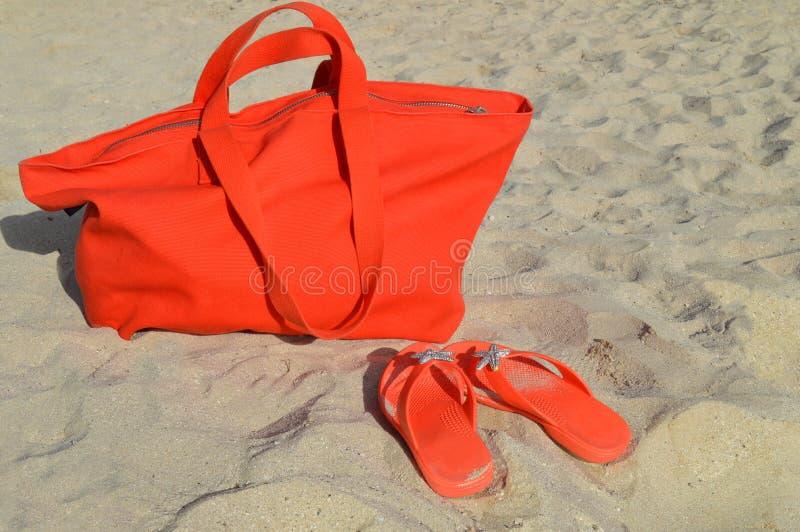 Orange beach bag and flip flops stock images
