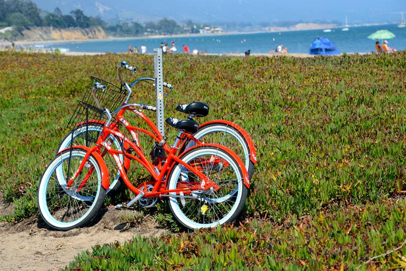 Red bikes. Orange beach cruiser bikes parking at the beach stock photos