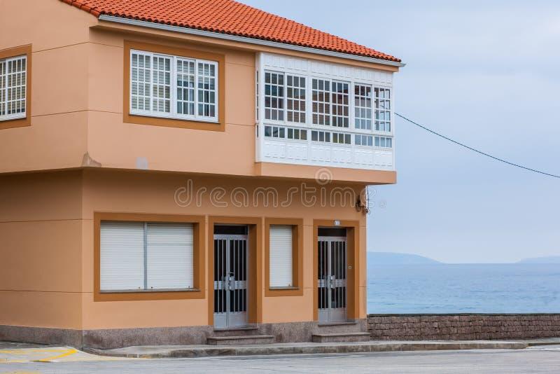 Orange beach house with blue sky near ocean stock photo