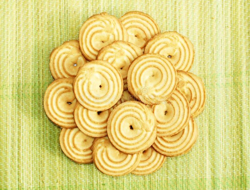 Orange beige color bright cookies arrangeras som en blomma på en grön gul strandmat arkivfoto