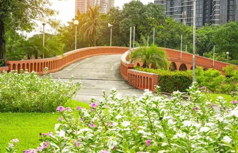 Orange Betonbogenkurvenbrige und -see in einem schönen Garten, frischen in Rosa- und weißenwestindischen perwinkle Blumenblättern stockfotografie