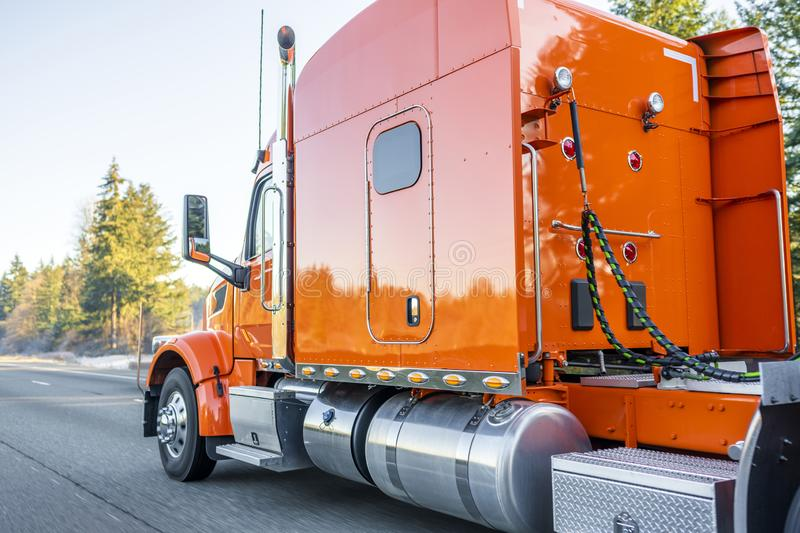 Orange big rig classic semi truck tractor with reflection driving on straight highway road. Bright orange classic iconic American big rig long haul professional royalty free stock images
