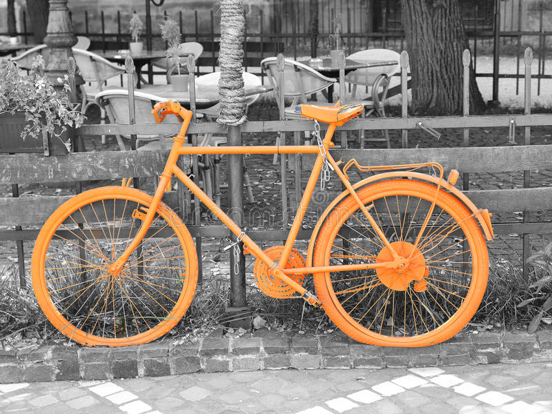 Orange bike. B&w photo of old orange bike on the fence of the coffee shop royalty free stock photo