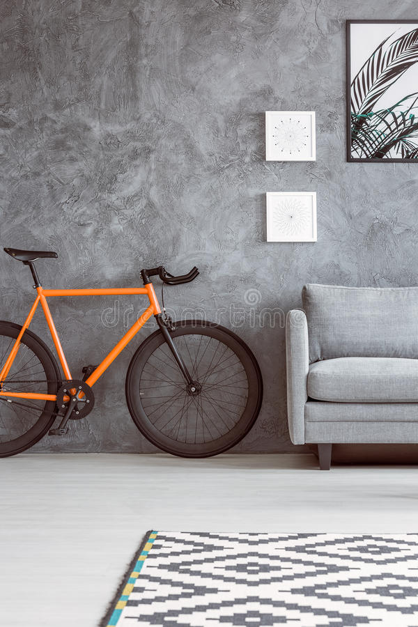 Orange bike next to sofa. Orange bike next to grey sofa in living room with black and white carpet and posters on concrete wall stock photos