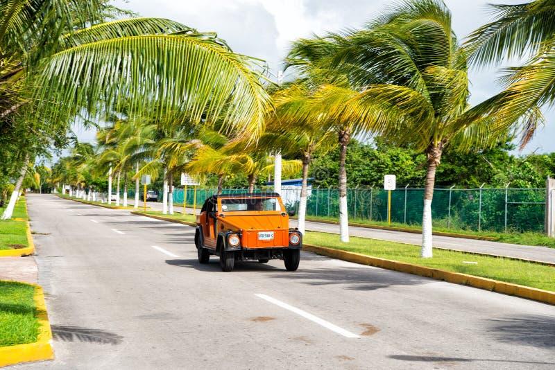Orange bil med manchauffören på vägen, Cozumel, Mexico arkivbild