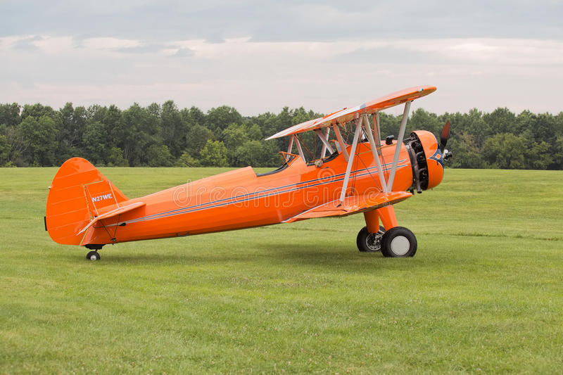 Orange Biplane. On green field ready for takeoff stock images