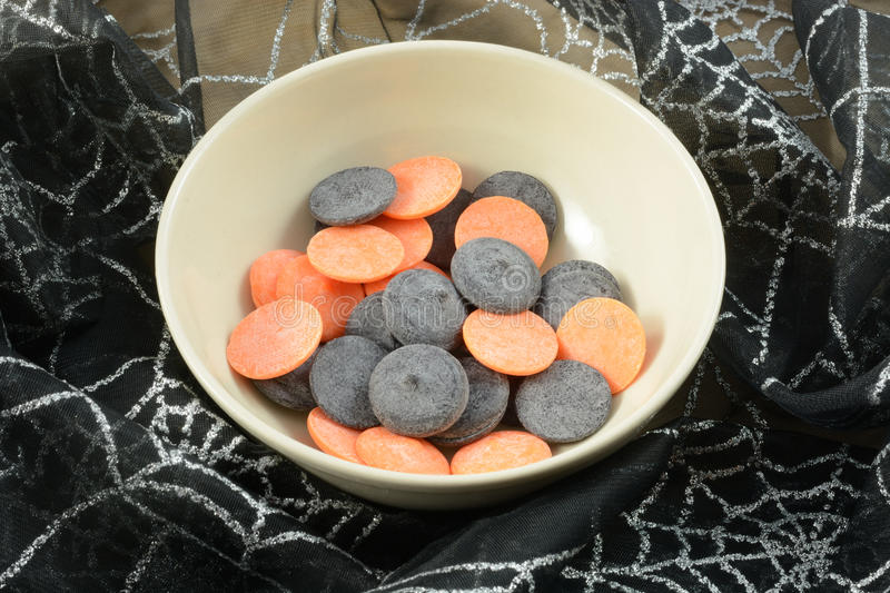 Orange and black colored white chocolate candy discs stock images