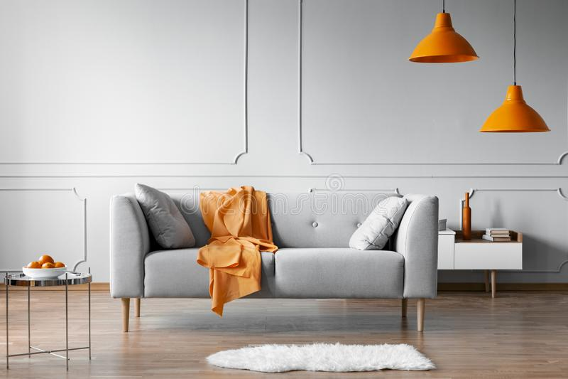 Orange blanket on grey scandinavian sofa, copy space on grey living room wall. Real photo stock photos