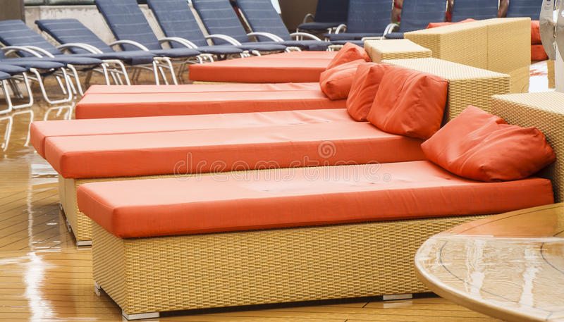 Orange and blue chaise lounges on a wet deck stock photos for Chaise longue orange
