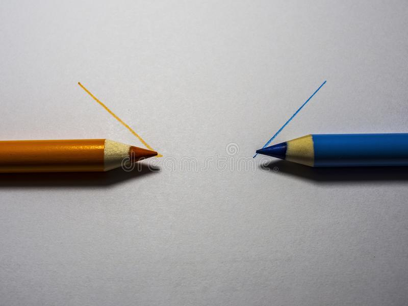 orange and blue crayon on a white background royalty free stock photography