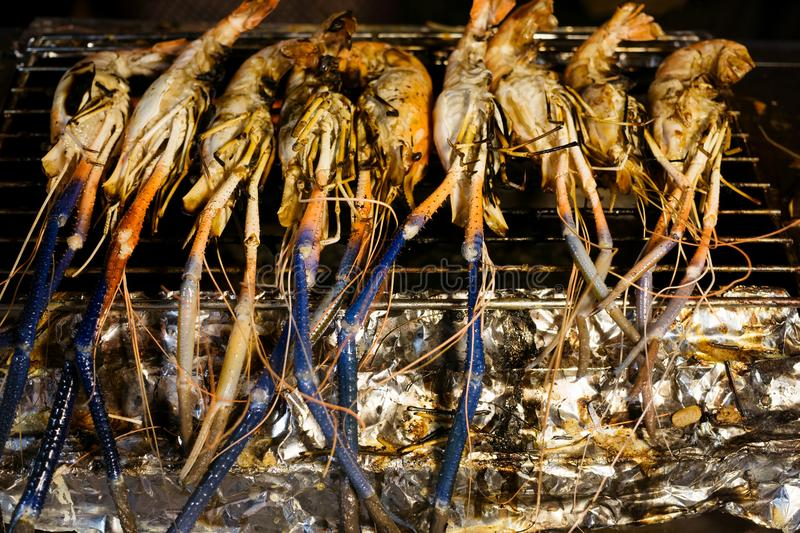 Orange and blue fresh water shrimps on grill at thai night market in Chiang Mai, Northern Thailand. Travel concept stock photo