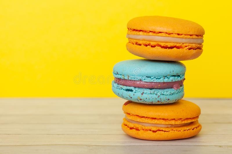 Orange and blue macaroons on yellow background, French cookies as a treat for the holiday royalty free stock photos