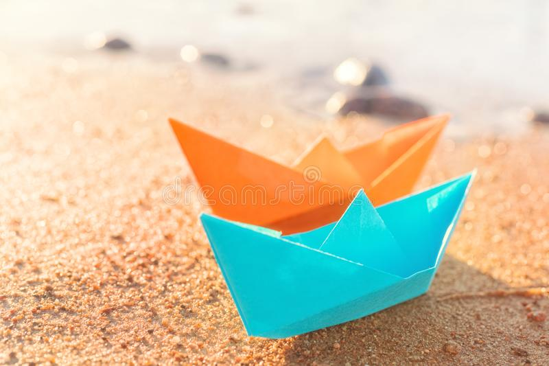 Orange and blue paper boats on sandy beach outdoors royalty free stock photo
