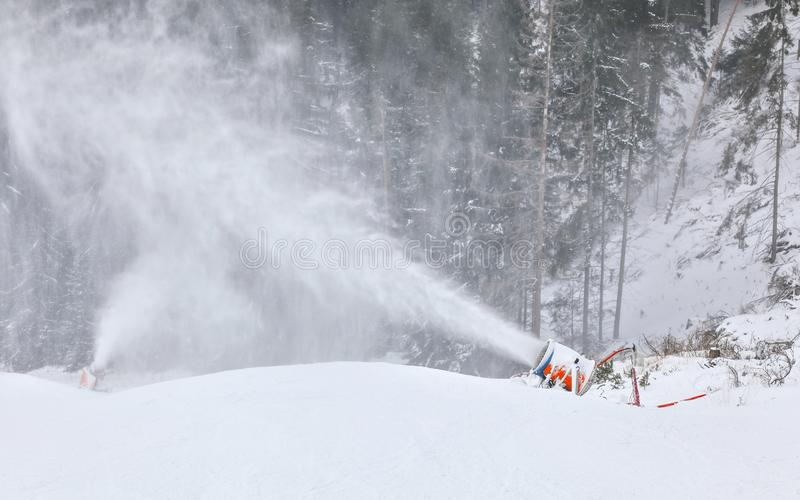 Orange and blue snow making cannon spreading ice crystals over ski piste, trees in background.  royalty free stock images