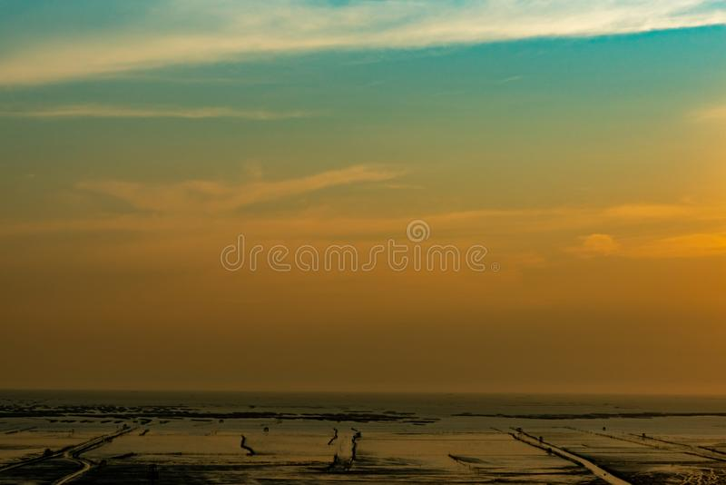 Orange and blue sunset sky and clouds. Sunset at the beach. Mud beach at seashore. Beautiful skyline at dusk. Landscape of muddy royalty free stock images