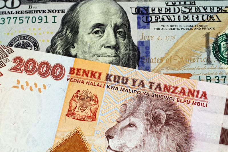 A Tanzanian shilling bank note with an American one hundred dollar bill. An orange and blue two thousand Tanzanian shilling bank note with a United States blue stock photography