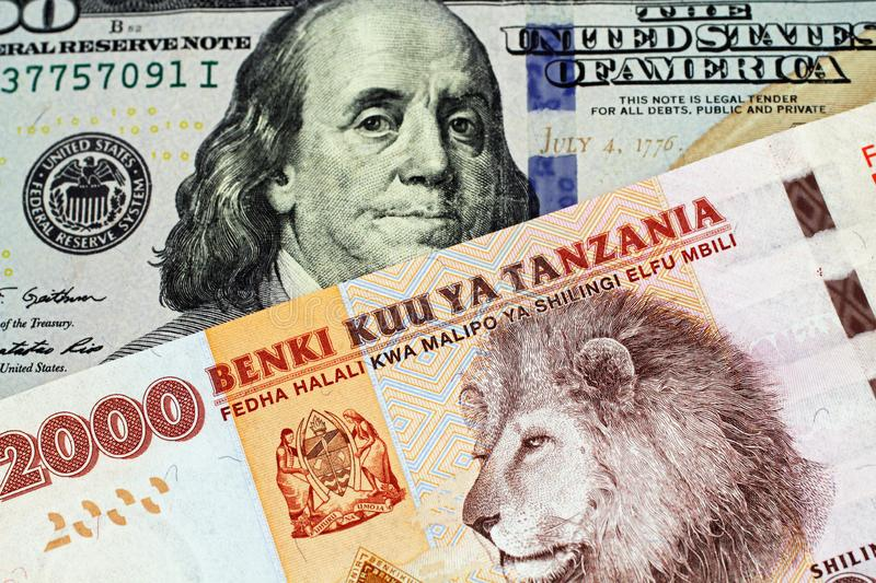 A Tanzanian shilling bank note with an American one hundred dollar bill. An orange and blue two thousand Tanzanian shilling bank note with a United States blue stock photo