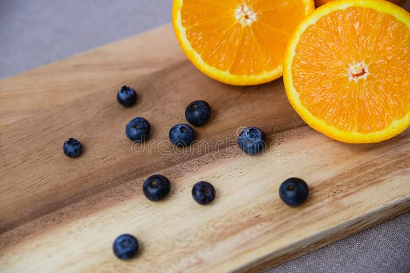 Orange and blueberries on Wooden Cutting Board royalty free stock photos