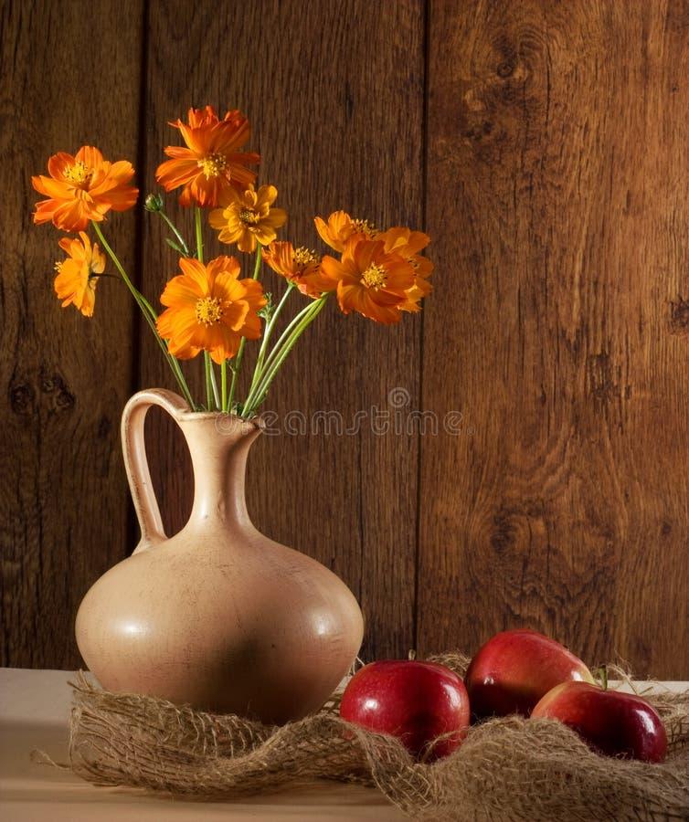 Orange Blumen und Äpfel lizenzfreie stockfotografie