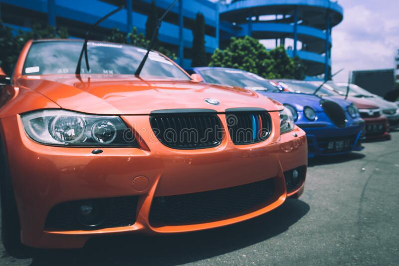Orange Bmw Car Beside Blue Bugatti Car royalty free stock image