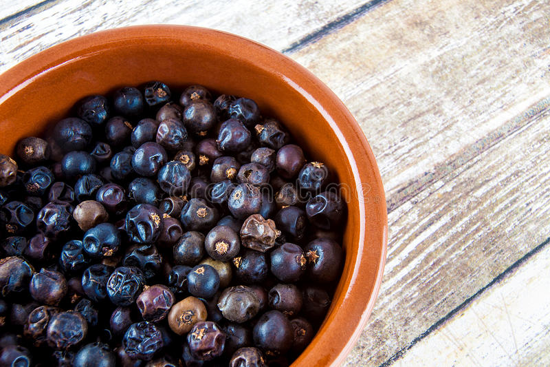 Orange bowl of juniper berries stock photos