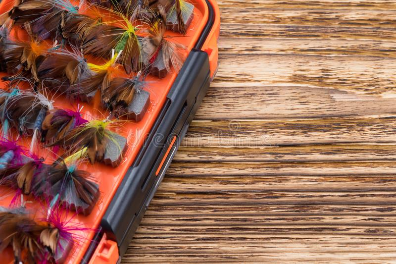Orange box with nozzles for fishing on a wooden background royalty free stock photos