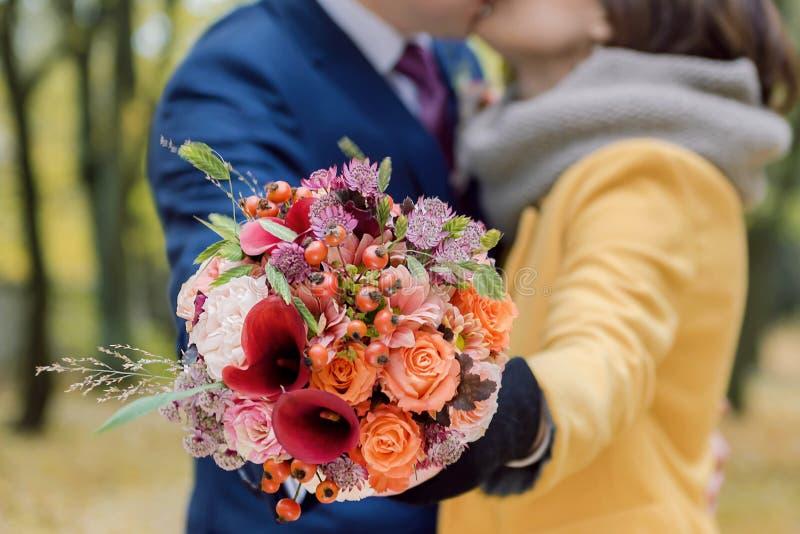 Orange bröllopbukett i händer royaltyfria bilder