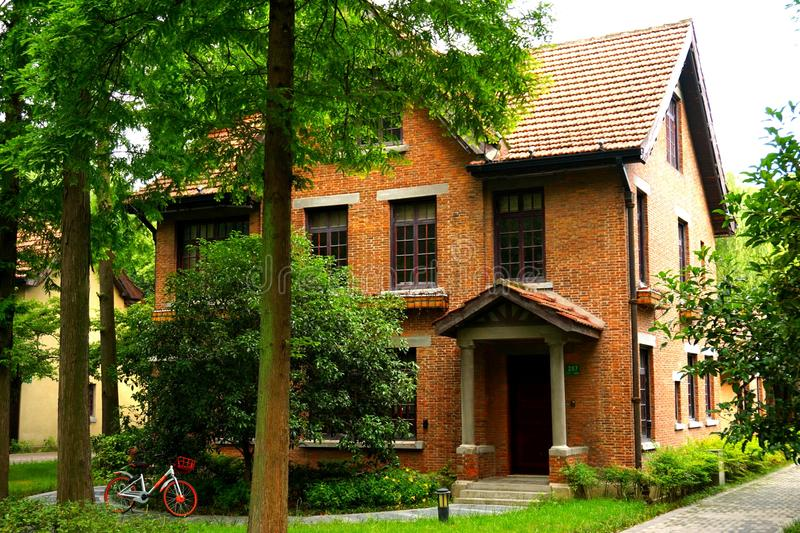 An Orange brick European style house in the woods. In the image, there is an orange brick European style house stock photography