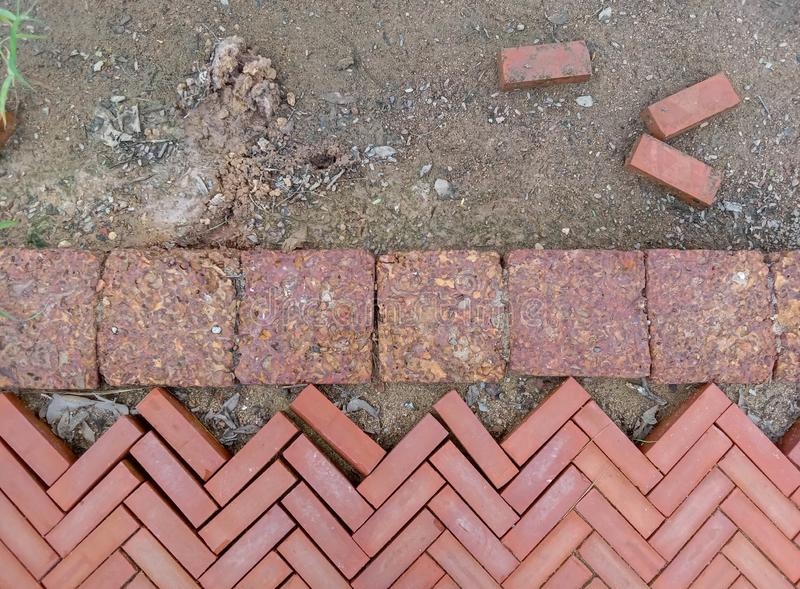 Orange brick floor with rough ground. Background of orange brick in zigzag pattern and split bricks on the rough ground with dry leaves and pebble royalty free stock photography