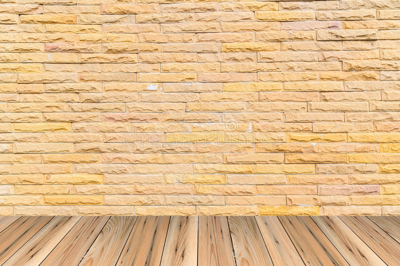 Orange brick wall as a nicely textured background on wood floor stock photography
