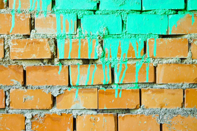 Orange brick wall colored with paint dripped royalty free stock image