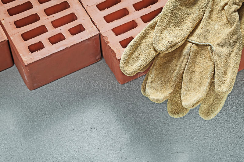 Orange bricks leather working gloves on concrete surface buildin. G concept stock photography