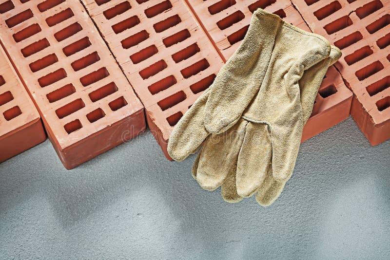 Orange bricks leather working gloves on concrete surface constru. Ction concept royalty free stock image