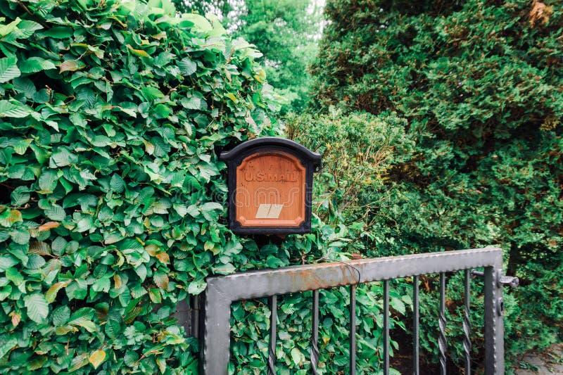 Orange Briefkasten auf Metallzaun mit gr?nem Blatthintergrund stockfotografie