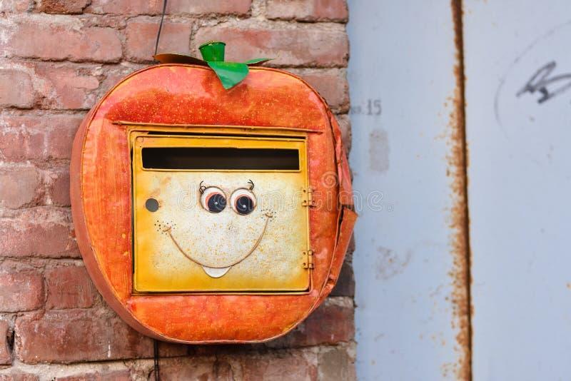 Orange Briefkasten mit Lächeln, Briefkasten, der an der Wand hängt stockfotografie