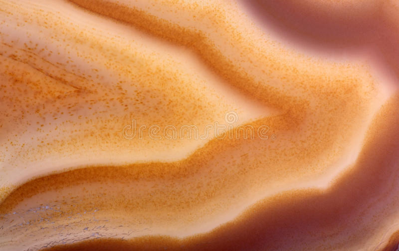 Orange and brown waves of agate structure. Background with yellow agate structure stock photos