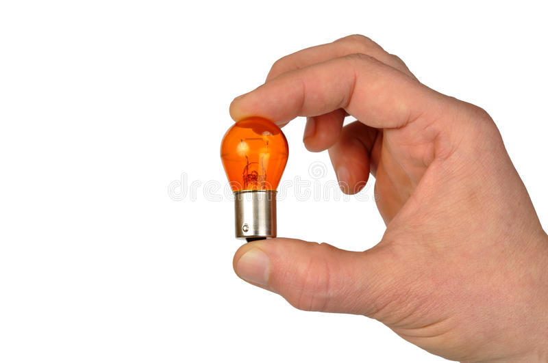 Orange Bulb. Hand with orange car bulb isolated on white stock images